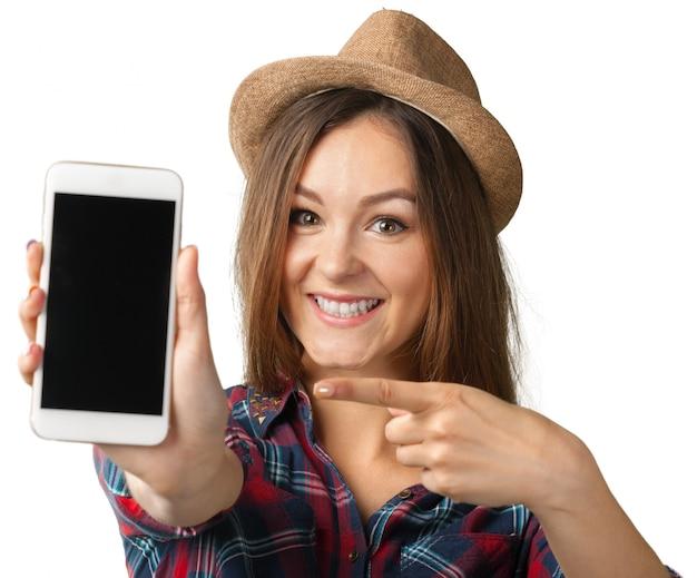 Счастливая усмехаясь женщина показывая мобильный телефон изолированный в белизне