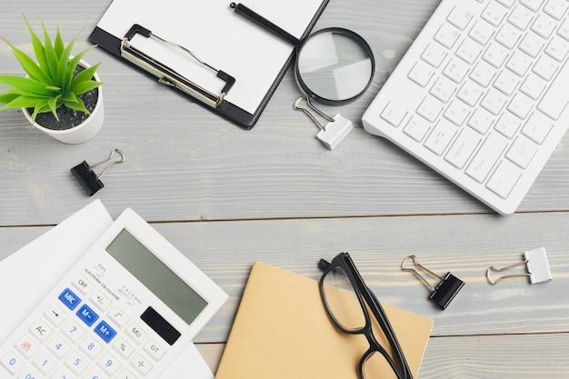 メガネと文房具と木製のデスクトップの平面図をクローズアップ。モックアップ
