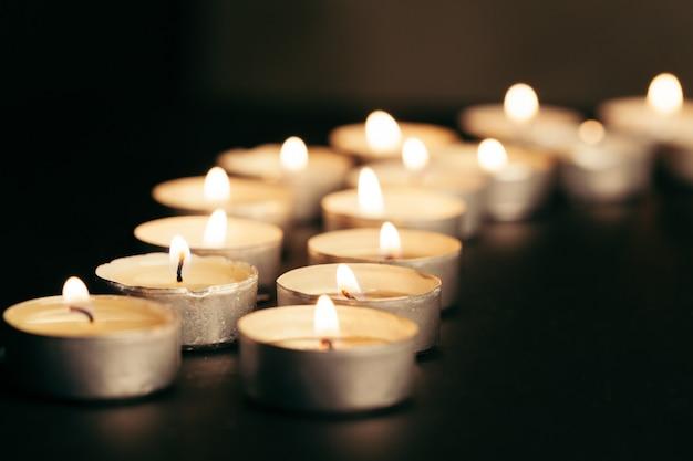 暗闇の中、テーブルの上のテキストのためのスペースで燃えているキャンドル。葬儀のシンボル