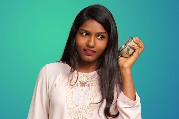 目覚まし時計を保持している疲れのインドの女性