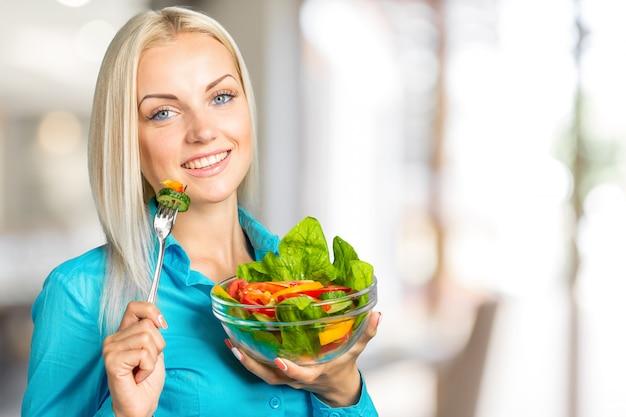 ボウルから新鮮なサラダを食べて幸せな遊び心のある女の子の肖像画