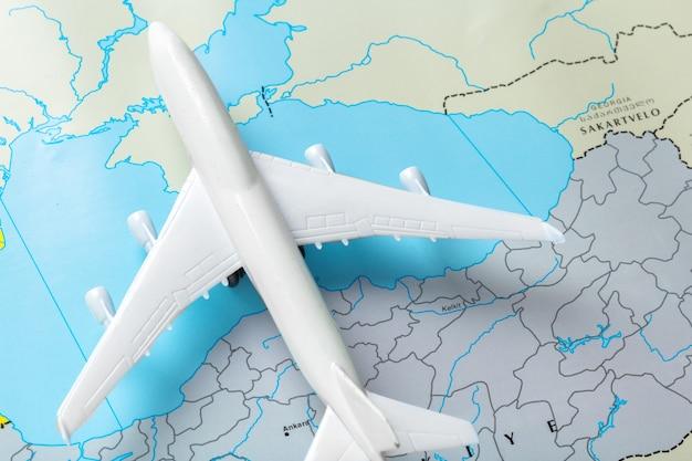 地図上を飛んでいる旅客機のミニチュア
