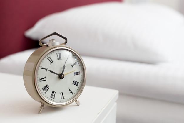 Винтажный будильник на кровати в гостиничном номере. проснись концепция вызова