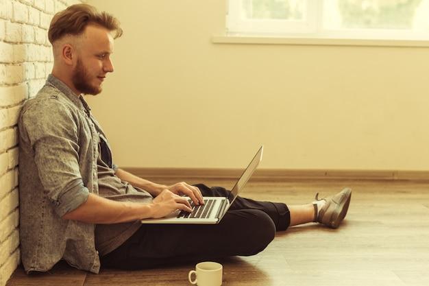 Молодой студент работает на своем ноутбуке дома