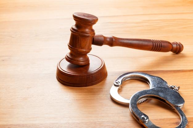小槌と木製のテーブルの上の手錠
