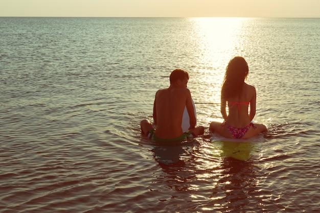 海でサーフボードに寄りかかってサーフィンカップル