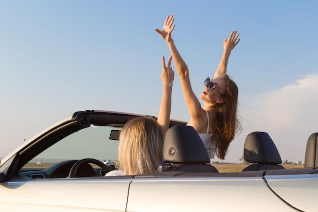 Две привлекательные молодые женщины в кабриолете