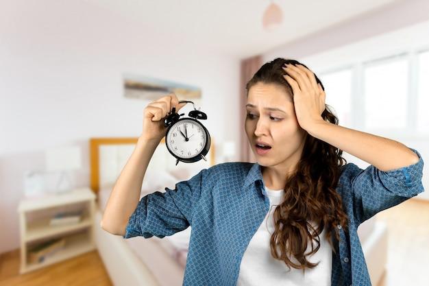 目覚まし時計を保持している女性