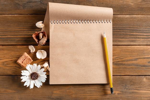 ビンテージの木製テーブルの上の花と空白のノートブック