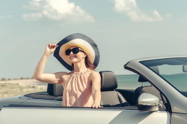 若い女性はビーチで車を運転します。