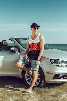 若い男がビーチで車を運転します。