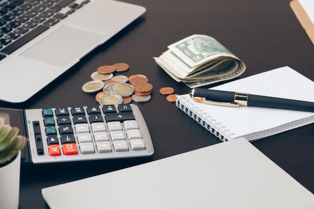 平均、財政、経済、家のコンセプト - お金を数えると自宅でメモを作る電卓のクローズアップ