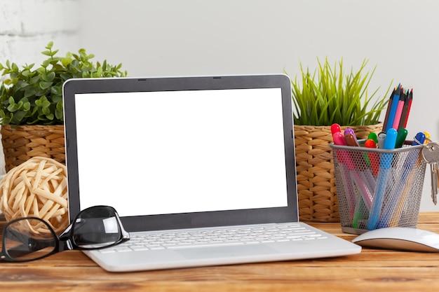 作業スペース、木製のテーブルの上のノートパソコンの空白の画面、