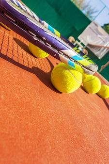 Теннисные мячи и ракетки на травяном корте