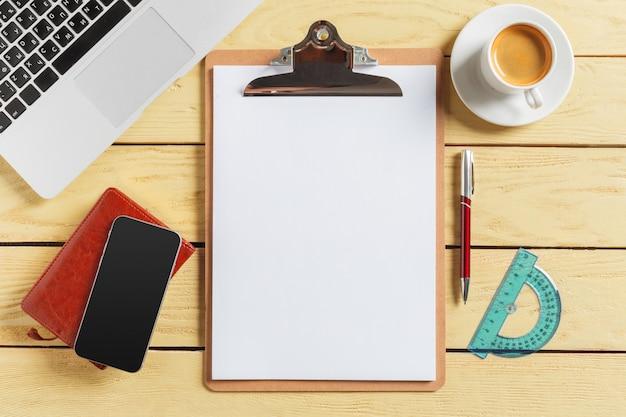 コーヒーカップ、鉛筆、コンピューターのキーボードのオフィステーブル