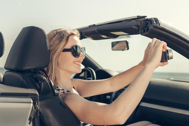 若い女性はビーチで車を運転します