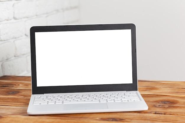 木製のテーブルにノートパソコンの空白の画面