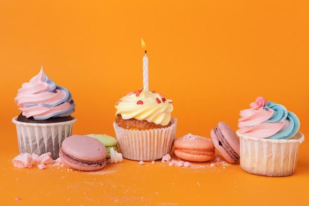 オレンジ色の背景に誕生日の蝋燭とカップケーキ