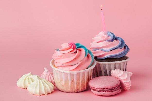 明るいピンクの背景においしいカップケーキをクローズアップ