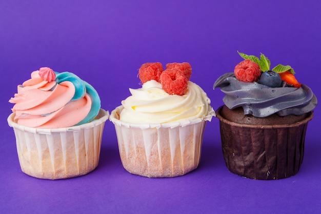 飽和の暗い紫色の背景に対して美しいカップケーキ