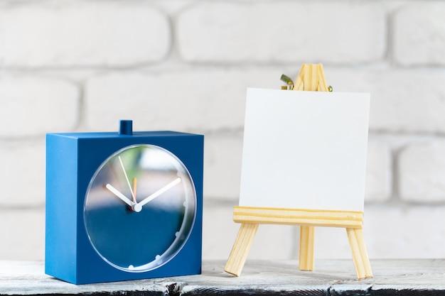 木製テーブルの上のイーゼルに空白のミニキャンバス、コピースペース
