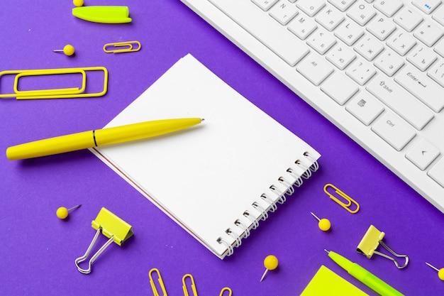 紫色の背景にオフィスライフスタイルアイテムの組成、オフィスの机の上のコンピューターキーボード事務用品
