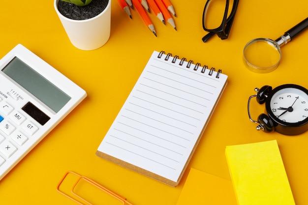 さまざまな文房具のトップビューでスタイリッシュな乱雑な黄色のデスクトップ