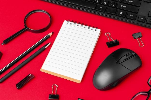 赤いオフィスデスク上の文房具のセット