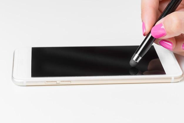 スマートな携帯電話にペンで働く女性