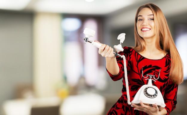 分離されたレトロな電話を持つ若い女性