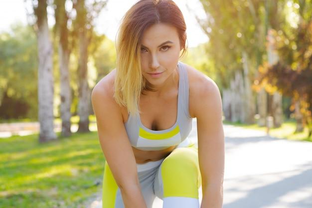 Спортивная женщина в позе бегущего старта в городском парке