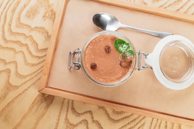 木製トレイにおいしいティラミスデザートをクローズアップ