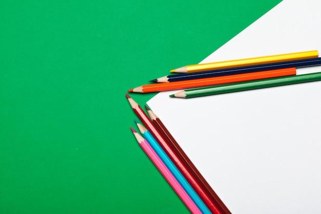 明るい緑色の紙にカラフルな鉛筆