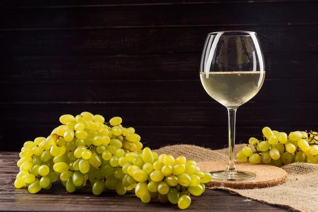 ワイングラスと木製のテーブルのブドウの房