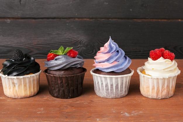 暗い-手作りの甘いデザートのおいしいラズベリーカップケーキ