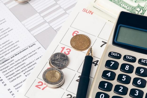 電卓とビジネス上のコインのクローズアップ