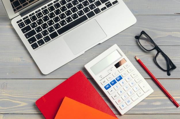 ラップトップコンピューターのキーボードと木製の机の上のさまざまな事務用品とメガネの斜めのビュー