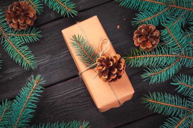 クリスマスギフトボックスと木製のテーブルにモミの木の枝。