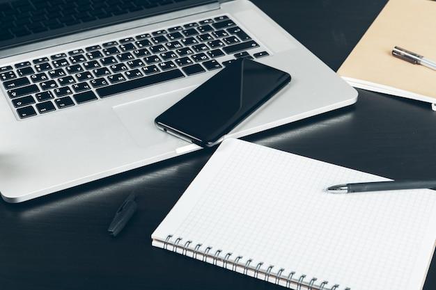 オフィステーブルの上のスマートフォンとコンピューターのキーボードをクローズアップ