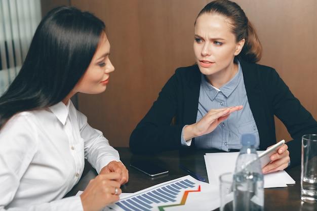 テーブルでノートパソコンで財務書類を探している女性