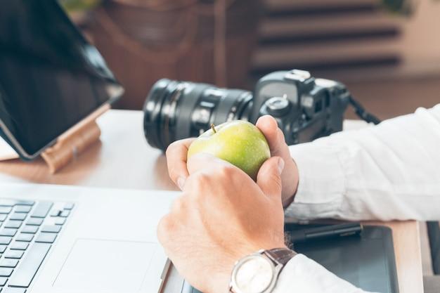 コンピューターに取り組んでいる若い男の写真家。キーボード、カメラ、ラップトップ、レンズを備えたワークデスク。