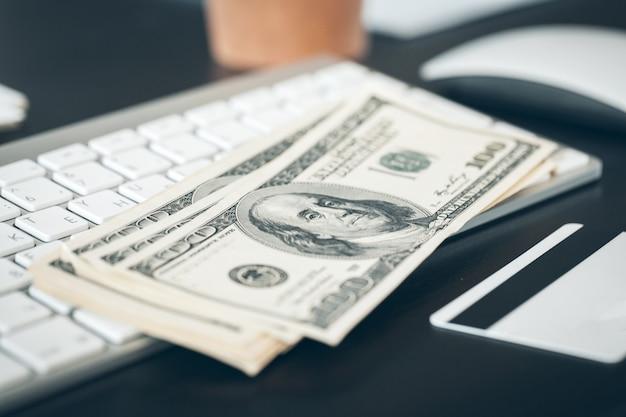 コンピューターのキーボードに置く米ドル紙幣をクローズアップ
