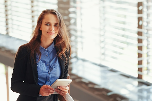 Бизнес-леди с цифровым планшетом в офисе