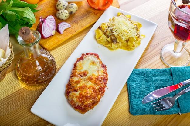 Курица пармиджана и спагетти заделывают на тарелку на столе.