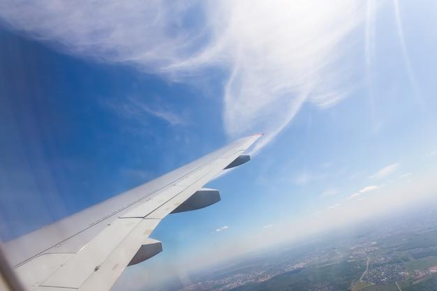 青い空と白い雲と飛行機の窓からの眺め