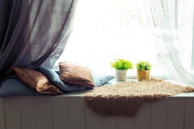 Уютное сиденье у окна с подушками
