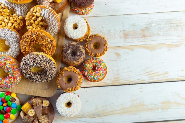 白い木の板においしいドーナツのコレクション