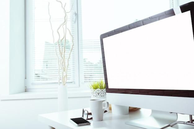 コンピューターの空白の画面を持つ作業テーブル