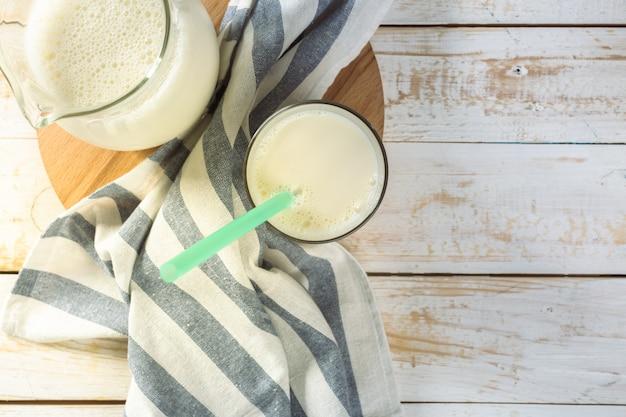 Парное молоко в стеклянном кувшине и стакан на деревянном фоне