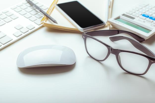 コンピューターのキーボード、消耗品、電卓、ペン、眼鏡を備えたオフィスデスクテーブル